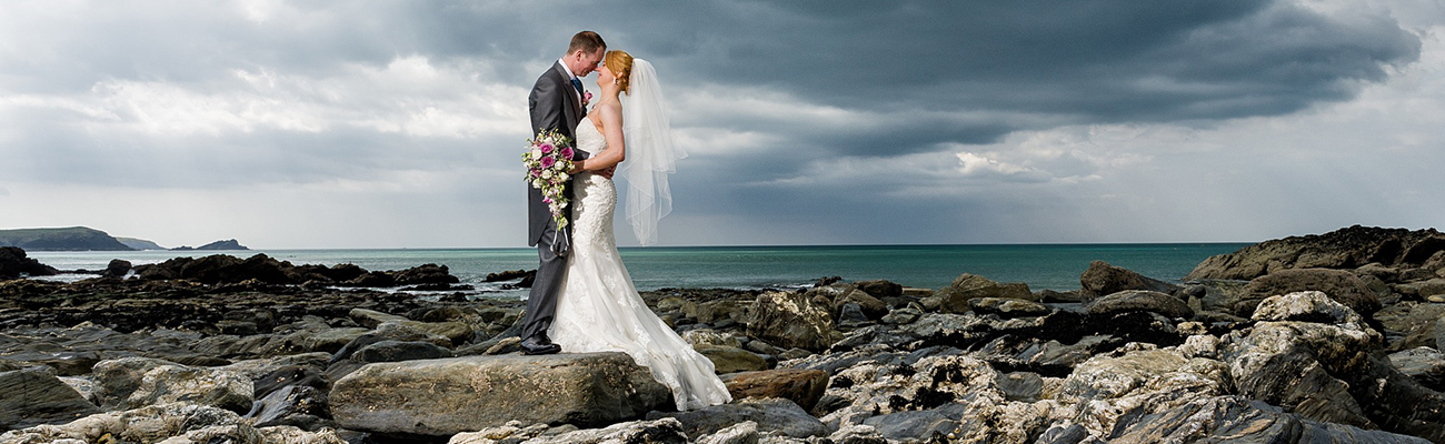 Couple kissing on Fistral Beach on their wedding day